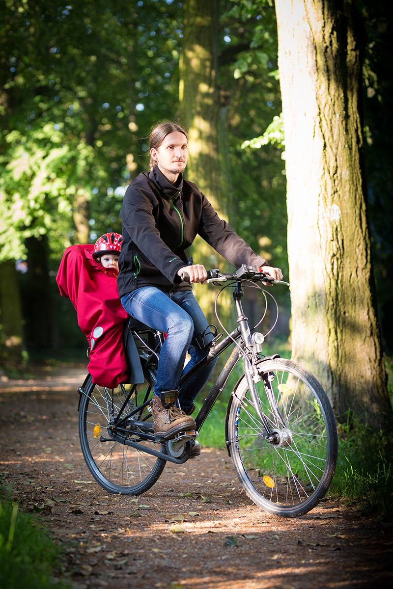 daddy and daughter on bike trip, wraped in red wichtelwarm cover